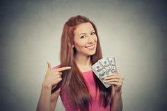 Riuscita tenuta della donna che mostra le banconote in dollari dei soldi Fotografie Stock