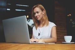 Riuscite free lance femminili che utilizzano NET-libro per il lavoro di distanza durante la prima colazione di mattina nel caffè Fotografia Stock