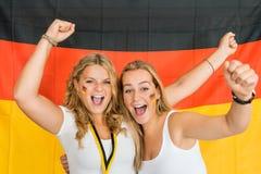 Riuscite sportive che gridano contro la bandiera tedesca Immagini Stock