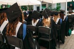 Riusciti laureati in vestiti accademici, alla graduazione, sedentesi Immagini Stock