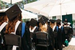 Riusciti laureati in vestiti accademici, alla graduazione, sedentesi Fotografia Stock Libera da Diritti