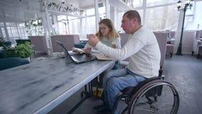 Riusciti proprietari di ristorante invalidi dell'uomo sulla sedia a rotelle con la donna che lavora al computer portatile per la  archivi video