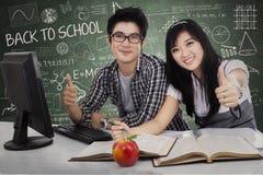 Riusciti studenti che mostrano il pollice in su Fotografia Stock