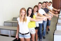 Riusciti studenti che tengono i pollici su Fotografia Stock