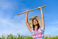 Riuscito agricoltore femminile che si alza estirpando zappa in un campo di grano Fotografie Stock
