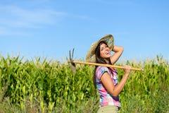 Riuscito agricoltore femminile con l'estirpazione della zappa in un campo di grano Immagini Stock