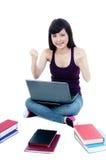 Riuscito allievo femminile con il computer portatile ed i libri Fotografia Stock