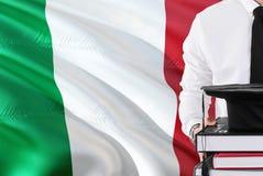 Riuscito concetto italiano di istruzione dello studente Tenuta i libri e del cappuccio di graduazione sopra il fondo della bandie immagine stock libera da diritti