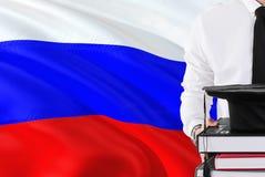 Riuscito concetto russo di istruzione dello studente Tenuta i libri e del cappuccio di graduazione sopra il fondo della bandiera  fotografia stock libera da diritti
