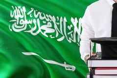 Riuscito concetto saudita di istruzione dello studente Tenuta i libri e del cappuccio di graduazione sopra il fondo della bandier fotografia stock