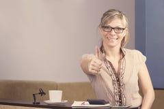 Riuscito: donna bionda felice che si siede con il calcolatore e che dà i pollici su Fotografia Stock