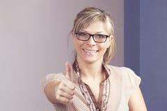 Riuscito: donna bionda felice che si siede con il calcolatore e che dà i pollici su Immagine Stock