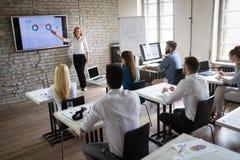 Riuscito gruppo di persone felice che imparano ingegneria del software ed affare durante la presentazione immagini stock libere da diritti