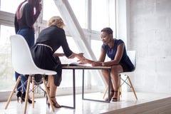 Riuscito gruppo femminile multietnico nello spazio coworking Ufficio dello spazio aperto immagine stock libera da diritti