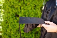 Riuscito laureato, in vestiti accademici, tenenti una graduazione c fotografia stock