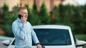 Riuscito maschio sicuro barbuto che parla facendo uso del colpo medio all'aperto dello smartphone archivi video