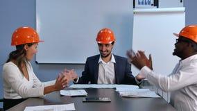 Riuscito nel gruppo multirazziale di affari degli ingegneri che celebrano successo che stringe le mani e sorridere video d archivio