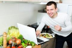 Riuscito piatto delle verdure dell'assaggio dell'uomo vicino al computer portatile Immagini Stock Libere da Diritti