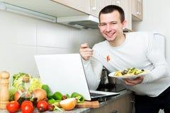 Riuscito piatto delle verdure dell'assaggio dell'uomo vicino al computer portatile Fotografia Stock