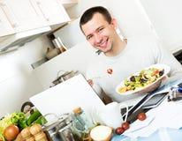 Riuscito piatto delle verdure dell'assaggio dell'uomo vicino al computer portatile Immagini Stock