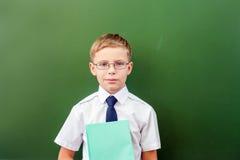 Riuscito scolaro che sta vicino alla lavagna nell'aula della scuola Fotografia Stock Libera da Diritti