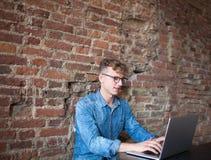 Riuscito scrittore di vendita del giovane che lavora al computer portatile portatile Fotografie Stock Libere da Diritti