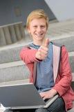 Riuscito studente adolescente con il pollice-su del computer portatile Immagini Stock Libere da Diritti