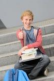 Riuscito studente con i libri ed il pollice-su del computer portatile Fotografie Stock Libere da Diritti