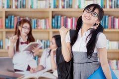 Riuscito studente con il suo gruppo in biblioteca Fotografie Stock