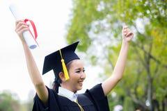 Riuscito studente di laurea con il fondo della natura, ragazza felice dello studente graduato Immagine Stock