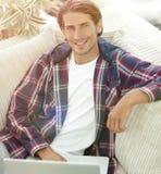 Riuscito tipo che lavora al computer portatile e che esamina macchina fotografica Vista per Immagine Stock