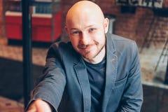 Riuscito uomo barbuto calvo adulto attraente sorridente in vestito con il computer portatile che dà stretta di mano, mano di aiut fotografia stock libera da diritti