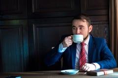 Riuscito uomo bello ricco in un caffè bevente del vestito Fotografie Stock