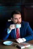 Riuscito uomo bello ricco in un caffè bevente del vestito Immagine Stock Libera da Diritti
