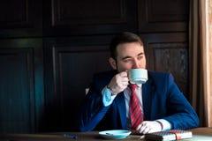 Riuscito uomo bello ricco in un caffè bevente del vestito Immagine Stock