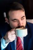 Riuscito uomo bello ricco in un caffè bevente del vestito Immagini Stock