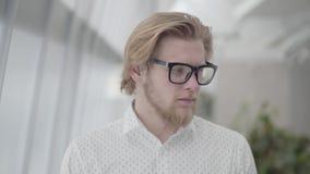 Riuscito uomo biondo del ritratto in vetri che stanno in un ufficio comodo leggero che esamina la macchina fotografica handsome video d archivio
