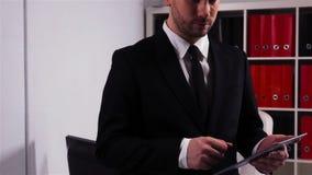 Riuscito uomo d'affari con il computer della compressa in ufficio video d archivio