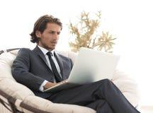 Riuscito uomo d'affari con il computer portatile che si siede in un grande armchai comodo Fotografia Stock