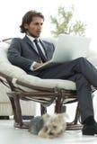 Riuscito uomo d'affari con il computer portatile che si siede in un grande armchai comodo Immagini Stock Libere da Diritti
