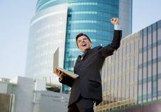Riuscito uomo d'affari con il segno facente felice di vittoria del computer portatile del computer fotografie stock