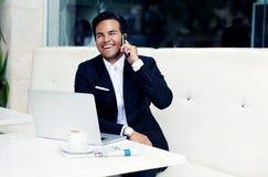 Riuscito uomo d'affari sorridente che si siede nel ristorante costoso moderno con il computer portatile e la tazza di caffè apert Fotografia Stock Libera da Diritti