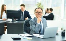 Riuscito uomo d'affari sul posto di lavoro con il computer portatile immagine stock