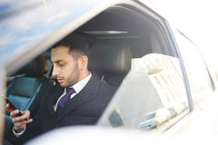 Riuscito uomo d'affari Using Smartphone dentro l'automobile immagini stock libere da diritti