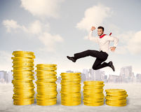 Riuscito uomo di affari che salta su sui soldi della moneta di oro Fotografia Stock Libera da Diritti