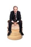 Riuscito uomo di affari che si siede su un mucchio delle monete fotografie stock libere da diritti