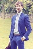 Riuscito uomo felice di affari che sta in un parco, sorridente esaminando macchina fotografica Ritratto dell'annata fotografia stock