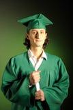 Riuscito uomo felice il suo giorno di graduazione nel verde Fotografie Stock