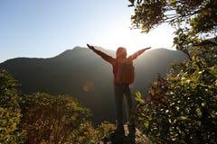 Riuscito viaggiatore con zaino e sacco a pelo della donna a braccia aperte sul picco di montagna Immagini Stock Libere da Diritti