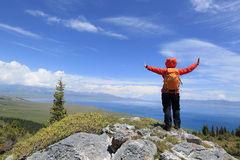 Riuscito viaggiatore con zaino e sacco a pelo della donna a braccia aperte sul picco di montagna Fotografia Stock